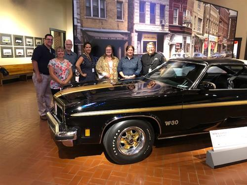 Students, Staff, and Designers around car at Gilmore Car Museum