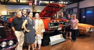 Students, Teachers, and Designers around a car at the Gilmore Car Museum.