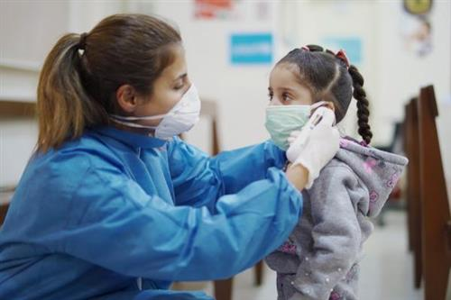 Nurse helping child with mask