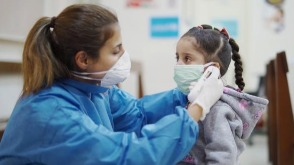 Nurse wearing PPE taking temperature of a child