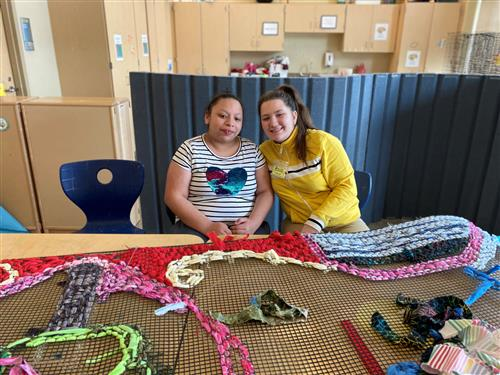Student and Mentor work on weaving project