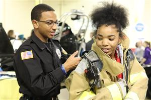 CTE Law Enforcement student helps an eighth grader try on fire equipmentat MiCareerQuest Southwest.