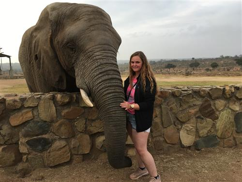 EFE Student posing by a South African elephant