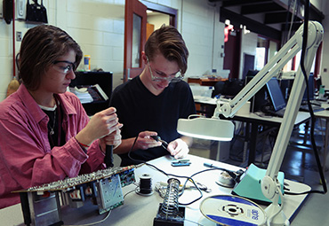 Two students engage in hands-on learning in the EFE/CTE Electronics & Robotics course.