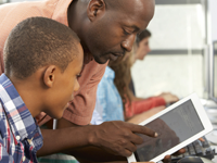Male teacher working with student on a tablet